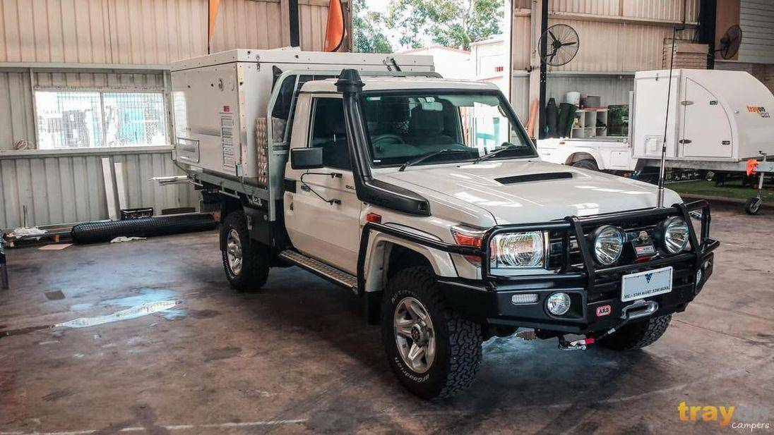 79 Series Landcruiser Ute Driving Performance. White single cab Toyota with UHF antenna and Snorkle with Trayon Camper on the Tray