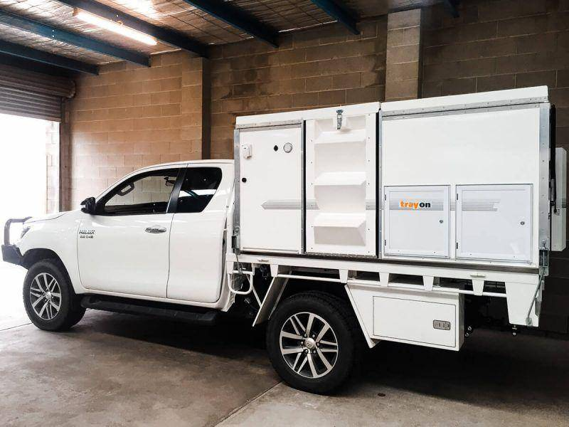 White extra Cab Toyota Hilux parked in Garage 2019 with Trayon Slide on Camper