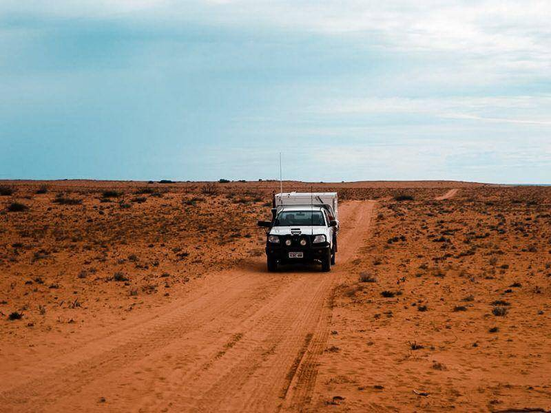 2015 Toyota Hilux crossing a desert road with a Trayon slide on camper