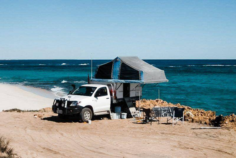 Single Cab Toyota Hilux at beach, offroad camping setup with a Trayon Slide on Camper