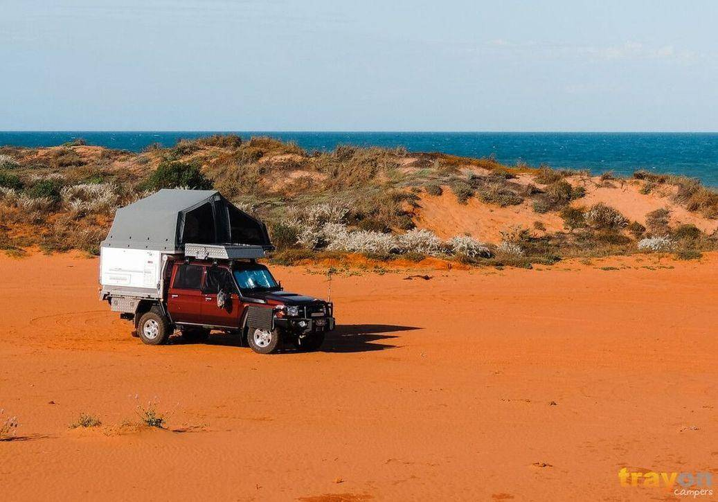 Dual Cab Toyota 79 Series Landcruiser on Red sand by the beach with a Trayon Slide on Camper