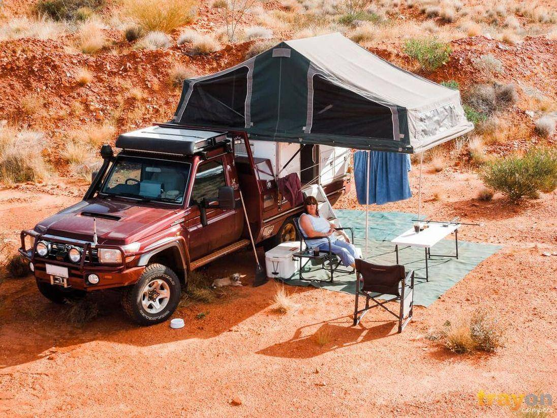 Dual Cab Toyota 79 Series Landcruiser on Red sand with a Trayon Slide on Camper. Camper relaxing with esky.