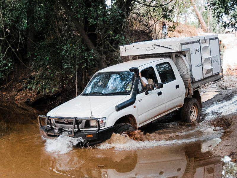 White Dual Cab Toyota Hilux 4x4 River Crossing, snorkle and Trayon ute back camper.